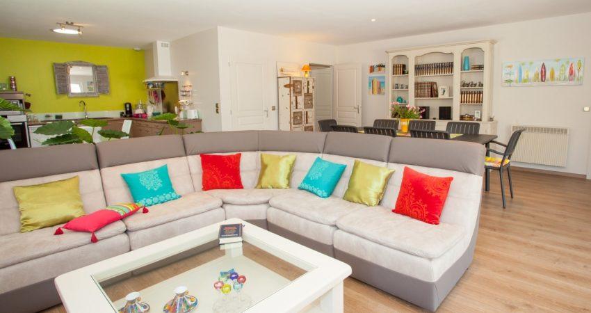 Salon et salle à manger avec un grand canapé et ses coussins de couleurs