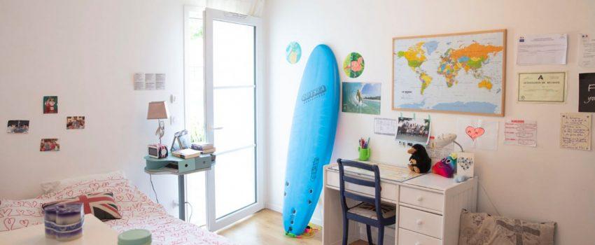 Chambre d'adolescent avec une porte fenêtre, une planche de surf et un bureau